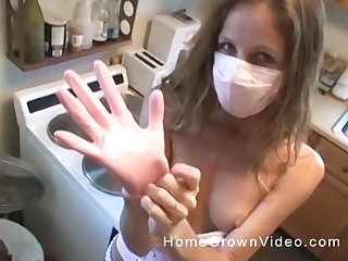 Unusual blonde housewife puts on a mask and gloves and strokes a flannel